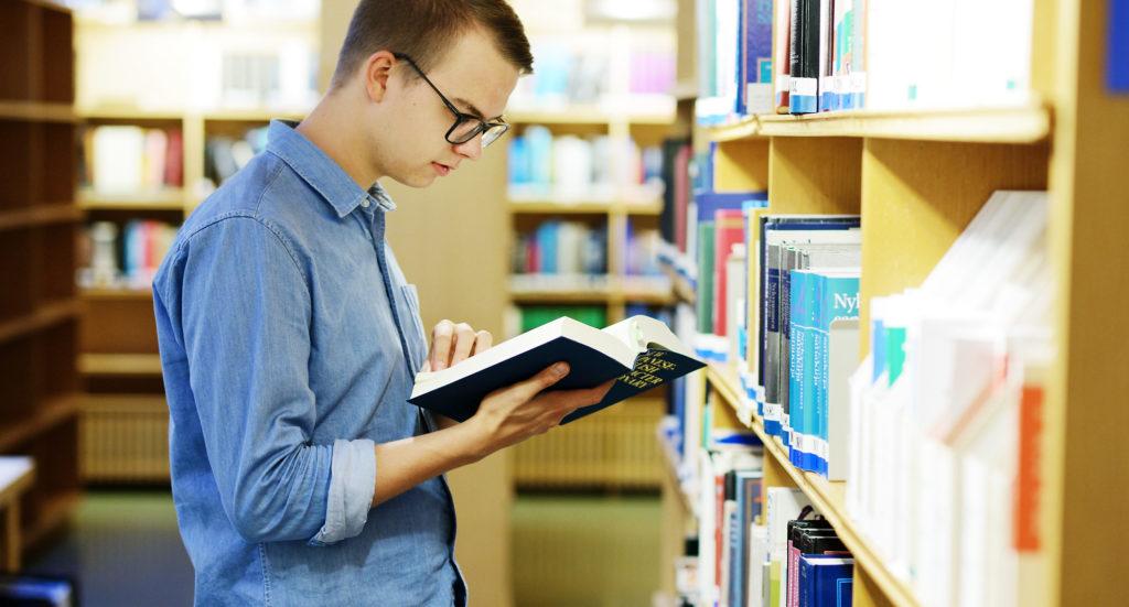 Opiskelija selailee kirjaa kirjastossa.